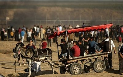 Young men ride a cart pulled by a donkey during confrontation between Palestinian demonstrators and Israeli troops east of Gaza City, along the border between the Gaza strip and Israel, on June 29, 2018. (AFP PHOTO / MAHMUD HAMS)