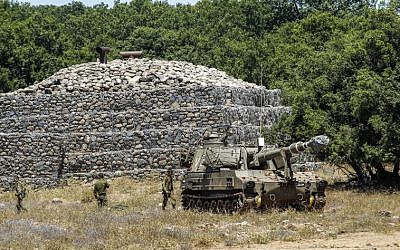 IDF soldiers walk past a bunker with a mobile artillery piece deployed near the border with Syria on the Israeli Golan Heights on July 1, 2018. (AFP Photo/Jalaa Marey)
