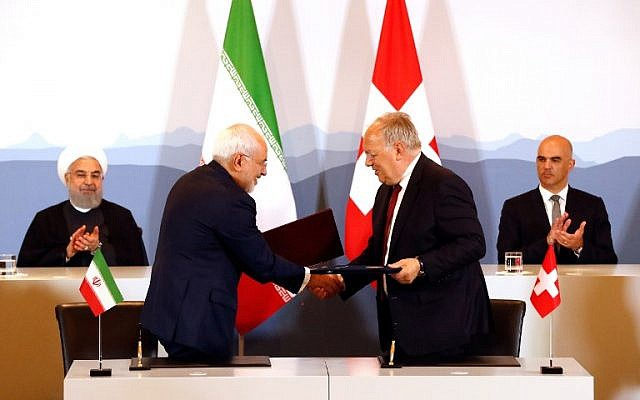 Iranian President Hassan Rouhani (top- L) and Swiss President Alain Berset (top-R) clap as Iranian Foreign Minister Mohammad Javad Zarif (L) and Swiss Economic Minister Johann Schneider-Ammann shakes hands after signing an agreement in Bern on July 3, 2018. (AFP Photo/Ruben Sprich)