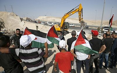 Demonstrators wave Palestinian flags as they protest against the upcoming demolition of the West Bank Bedouin village of Khan al-Ahmar on July 4, 2018. (AFP Photo/Abbas Momani)
