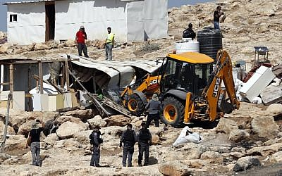 Israeli police secure a bulldozer demolishing structures at the Bedouin village of Abu Nuwar, east of Jerusalem in the West Bank on July 4, 2018. (AHMAD GHARABLI/AFP)