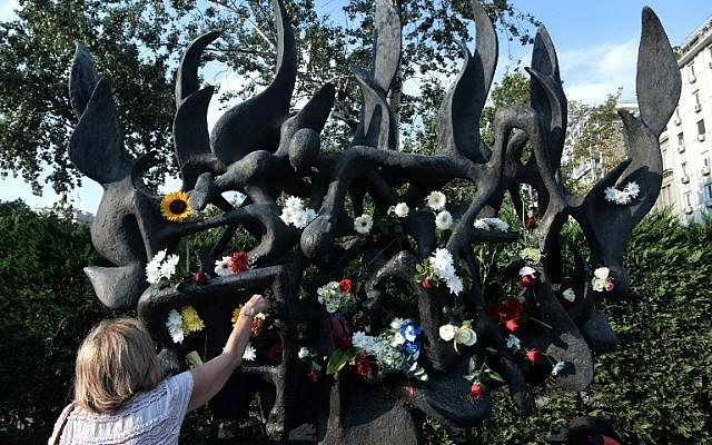 A woman places a flower on the Holocaust memorial in Thessaloniki, during a protest against its desecration, on July 4, 2018. (AFP/ Sakis Mitrolidis)