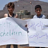 Displaced Syrian children hold signs during a protest in front of a UN base in the province of Quneitra, southwestern Syria, near the border with the Israeli Golan Heights, demanding the United Nations to help the stranded displaced in Syria-Israel and Syria-Jordan borders on July 4, 2018. (AFP PHOTO / Mohamad YUSUF)