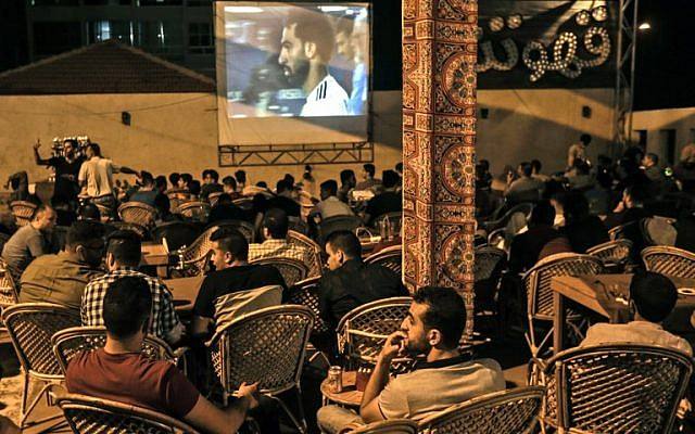 In this file photo taken on June 19, 2018 Palestinians watch on a big screen the Russia 2018 World Cup Group A football match between Russia and Egypt at at a coffeehouse in Gaza City. (AFP/Mahmud Hams)