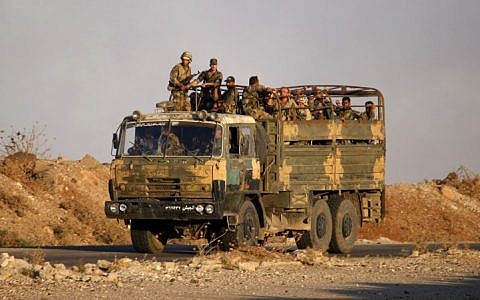 Illustrative: Syrian government soldiers ride in an army truck near the Nassib border crossing with Jordan in the southern province of Daraa on July 6, 2018. (AFP Photo/Mohamad Abazeed)