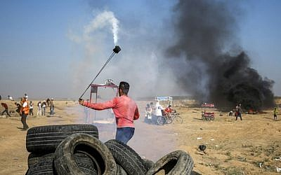 A Palestinian uses a slingshot to throw back a tear gas canister at Israeli forces during clashes along the border east of Gaza City on July 6, 2018. (AFP Photo/Said Khatib)