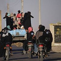 Syrians ride a vehicle carrying their personal belongings, as they return to their homes in towns and villages situated on the eastern outskirts of Daraa, on July 7, 2018. (AFP Photo/ Mohamad Abazeed)