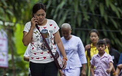 Relatives walk out from the cave complex after taking part in a prayer ceremony as rescue operations continue for the 12 boys and their football team coach trapped in Tham Luang cave in Thailand on July 7, 2018. (AFP PHOTO / YE AUNG THU)