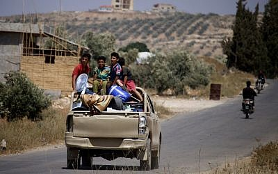 Syrians ride a vehicle carrying their personal belongings as they return to their homes in towns and villages situated on the eastern outskirts of Daraa on July 7, 2018. (AFP Photo/Mohamad Abazeed)
