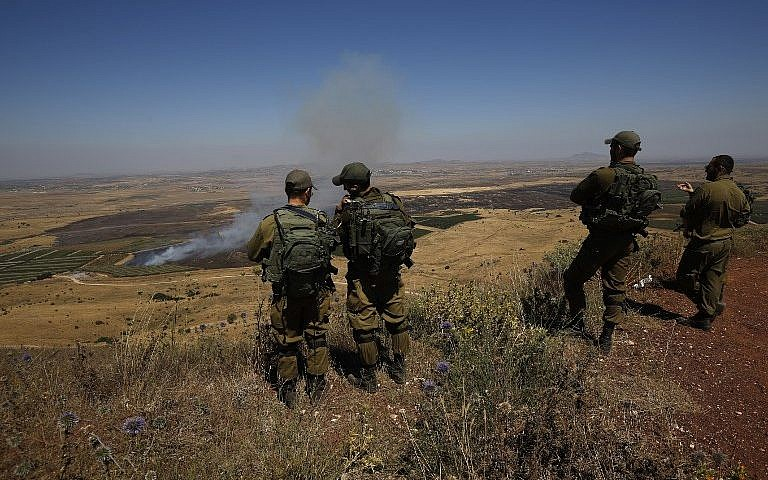 Israeli soldiers at an army base in the Golan Heights look out across the border with Syria