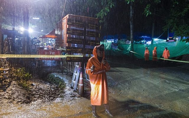 A Thai policeman guards an area under rainfall near the Tham Luang cave at the Khun Nam Nang Non Forest Park in Mae Sai district of Chiang Rai province on July 7, 2018, as rescue operation continues for the 12 boys and their football team coach. ( AFP PHOTO / Ye Aung THU)