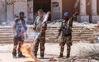 Syrian government soldiers burn an opposition flag while flashing the victory gesture at the Nassib border crossing with Jordan in the southern province of Daraa on July 7, 2018 (AFP PHOTO / Youssef KARWASHAN)