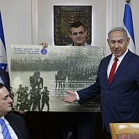 Israeli Prime Minister Benjamin Netanyahu receives a gift from the Ze'ev Jabotinsky Institute during the weekly cabinet meeting at his office in Jerusalem, July 8, 2018. (AFP PHOTO / POOL / ABIR SULTAN)