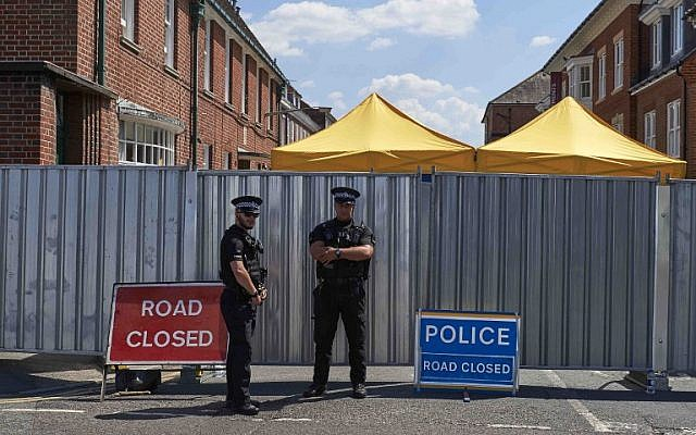 Police officers stand guard near barriers across Rollestone Street, outside the John Baker House Sanctuary Supported Living in Salisbury, southern England, on July 8, 2018. (AFP Photo/Niklas Halle'n)