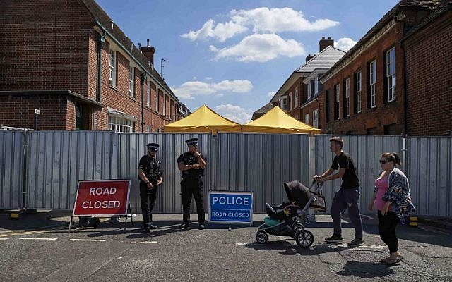 Pedestrians walk past police officers standing guard near barriers across Rollestone Street, outside the John Baker House Sanctuary Supported Living in Salisbury, southern England, on July 8, 2018. (AFP/ NIKLAS HALLE'N)
