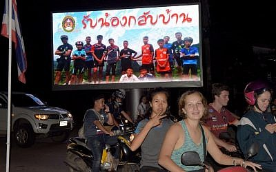 "Motorists pass a billboard with a photograph showing members of the Thai children's football team ""Wild Boar"" and their coach with a message ""welcome home brothers"" displayed in Chiang Rai as the boys and their coach were all rescued in the Tham Luang cave in Khun Nam Nang Non Forest Park in the Mae Sai district on July 10, 2018. (AFP PHOTO / TANG CHHIN Sothy)"