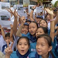 Thai students smile as they hold pictures of 12 boys and a football coach in front of the hospital where the group, who were rescued after being trapped in a nearby cave for 18 harrowing days, were brought for observation in the northern Thai city of Chiang Rai on July 11, 2018. (AFP Photo/Tang Chhin Sothy)