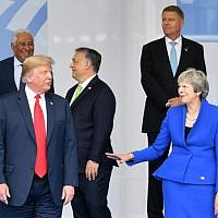US President Donald Trump (C) gestures as he poses alongside Britain's Prime Minister Theresa May (2R) and Iceland's Prime Minister Katrín Jakobsdóttir (R) during the opening ceremony of the NATO (North Atlantic Treaty Organization) summit, at the NATO headquarters in Brussels, on July 11, 2018. (AFP PHOTO / EMMANUEL DUNAND)