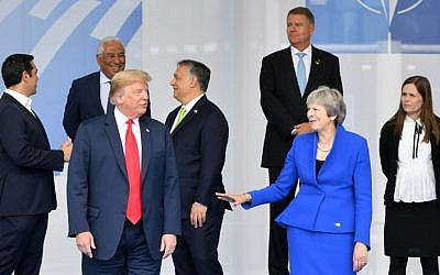 Illustrative: US President Donald Trump (C) gestures as he poses alongside Britain's Prime Minister Theresa May (2R) and Iceland's Prime Minister Katrín Jakobsdóttir (R) during the opening ceremony of the NATO (North Atlantic Treaty Organization) summit, at the NATO headquarters in Brussels, on July 11, 2018. (AFP PHOTO / EMMANUEL DUNAND)
