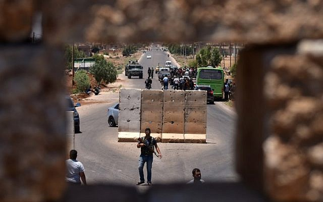 A bus stops at a checkpoint as displaced Syrians from the Daraa province come back to their hometown in Bosra, southwestern Syria, on July 11, 2018.  (AFP PHOTO / Mohamad YUSUF)