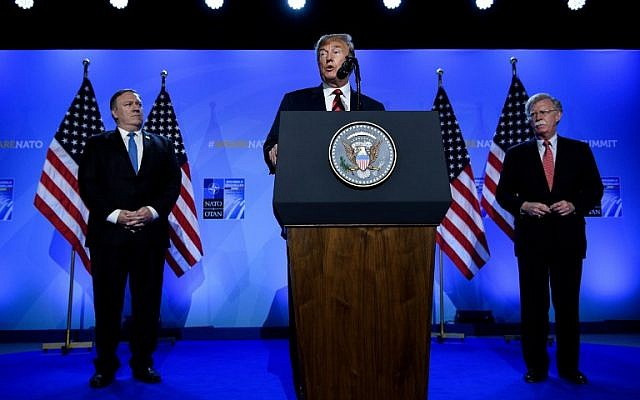 US President Donald Trump (C) is accompanied by US Secretary of State Mike Pompeo (L) and US National Security Adviser John Bolton (R) as he addresses a press conference on the second day of the North Atlantic Treaty Organization (NATO) summit in Brussels on July 12, 2018. (AFP PHOTO / Brendan Smialowski)