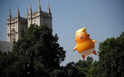 Pedestrians walk past as a giant balloon depicting US President Donald Trump as an orange baby floats next to the towers of Westminster Abbey during a demonstration against Trump's visit to the UK in Parliament Square in London on July 13, 2018. (AFP PHOTO / Tolga AKMEN)