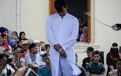 Onlookers watch as a member of Indonesia's Sharia police (R) whips a man (C) accused of having gay sex during a public caning ceremony outside a mosque in Banda Aceh, capital of Aceh province on July 13, 2018. (AFP/CHAIDEER MAHYUDDIN)