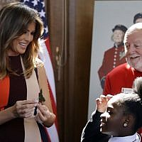 US First Lady Melania Trump (L) helps children make paper flowers as she meets British military veterans known as 'Chelsea Pensioners' during a visit to the Royal Chelsea Hospital in London on July 13, 2018. (AFP Photo/Pool/Luca Bruno)