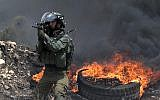 An Israeli soldier fires a rubber bullet towards Palestinian protesters during clashes  near Nablus, in the West Bank on July 13, 2018. ( AFP PHOTO / JAAFAR ASHTIYEH)