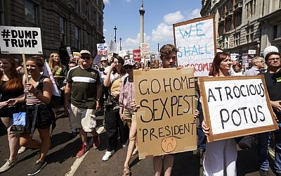 Protesters against the UK visit of US President Donald Trump hold up placards as they take part in a march and rally in London on July 13, 2018. (AFP PHOTO / Niklas HALLE'N)