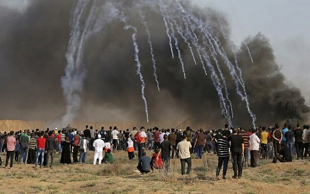 A picture taken on July 13, 2018 shows tear gas canisters fired by Israeli forces landing amidst protesters during a demonstration along the border with Israel east of Gaza City. (AFP/Mahmud Hams)