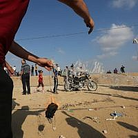 A Palestinian protestor prepares to attach an incendiary to a kite before flying it towards Israel on July 13, 2018 during a demonstration along the Israel-Gaza border fence east of Gaza City. (AFP PHOTO / MAHMUD HAMS)