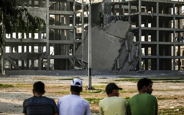Palestinian youths look at a building that was damaged by an Israeli air strike on a building in the Shati refugee camp in the northern Gaza Strip. July 14, 2018. ( AFP PHOTO / MAHMUD HAMS)
