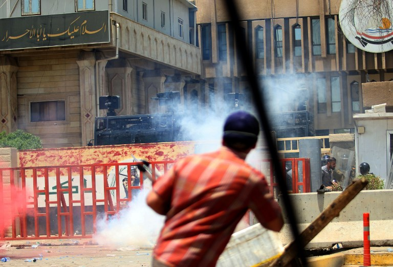 Iraqi riot police fire tear gas at protesters during a demonstration in Basra