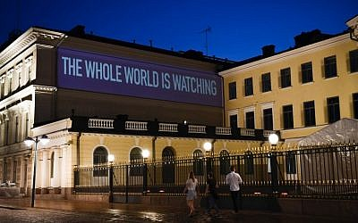 A sentence reading The Whole World is Watching is projected on the presidential palace on the eve of a summit between US President Donald Trump and Russian President Vladimir Putin in Helsinki on July 15, 2018. AFP / Jonathan NACKSTRAND)