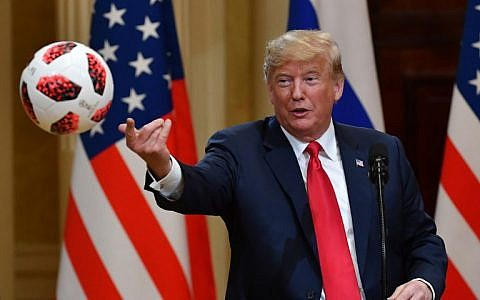 US President Donald Trump throws a soccer ball to his wife (unseen) from the 2018 football World Cup that he received from Russia's President Vladimir Putin during a joint press conference at the Presidential Palace in Helsinki, Finland, on July 16, 2018. (AFP Photo/Yuri Kadobnov)