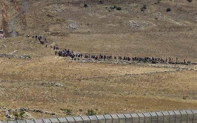 Syrians, displaced by fighting in the country's southwest, approach the border fence between Syria and Israel the Syrian village of Bariqu in the southern province of Quneitra, on July 17, 2018 (AFP /JALAA MAREY)