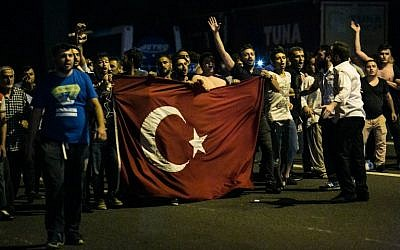 Illustrative photo of people shouting slogans as they carry a flag on a street near the Fatih Sultan Mehmet Bridge during clashes with military forces in Istanbul, July 15, 2016. (GURCAN OZTURK/AFP)