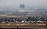 A picture taken on July 18, 2018, from the Israeli Golan Heights shows smoke rising above buildings during unidentified ai strikes across the border fence opposite a camp for displaced Syrians near the village of al-Rafeed in the southern Syrian province of Daraa. (AFP PHOTO / JALAA MAREY)