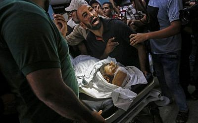Relatives mourn over the body of Abdel Karim Radwan, a Hamas military winge member who was killed in an Israeli air strike on a group launching fire balloons on July 19, 2018. (AFP PHOTO / SAID KHATIB)
