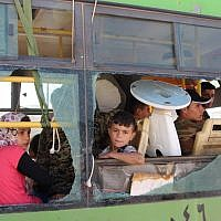 Illustrative image of evacuated Syrians from  the area of Fuaa and Kafraya in the Idlib province, looking out of a broken bus window during the evacuation of several thousand residents from the two pro-regime towns in northern Syria on July 19, 2018. (AFP/STR)