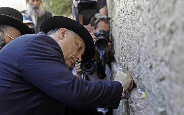 Hungarian Prime Minister Viktor Orban places a paper note at the Western Wall in Jerusalem's Old City during his visit to Israel on July 20, 2018. (AFP PHOTO / MENAHEM KAHANA)