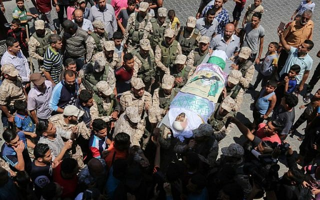 Hamas fighters and Palestinian men carry the body of Abdel Karim Ismail Radwan, who was reportedly killed in an Israeli airstrike, during his military funeral in Rafah in the southern Gaza Strip on July 20, 2018. (Said Khatib/AFP)