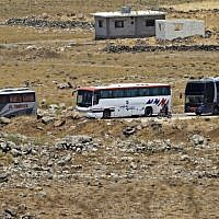 A picture taken on July 20, 2018, from the Israeli Golan Heights shows buses in a southwestern area of Syria that are transferring Syrian rebel fighters and civilians to opposition territory in Idlib further north. (AFP Photo/Jalaa Marey)