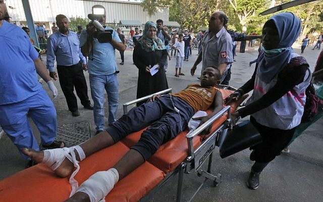 Palestinian paramedics push a youth, who was injurred during clashes near the border with Israel, as he lies on a gurney into a hospital in Khan Yunis in the southern Gaza Strip on July 20, 2018.( AFP PHOTO / SAID KHATIB)