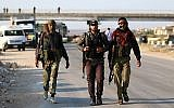 Syrian rebel fighters from the Quneitra province walk with their rifles as they wait at the Morek crossing point to be transfered in the provinces of Idlib and Aleppo on July 21, 2018. (AFP Photo/Aaref Watad)