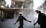 In this photo taken on October 5, 2016, Syrian civil defense volunteers, known as the White Helmets, work around destroyed buildings following reported airstrikes on the rebel-held town of Douma, on the eastern outskirts of the capital Damascus. (AFP PHOTO / Sameer Al-Doumy)