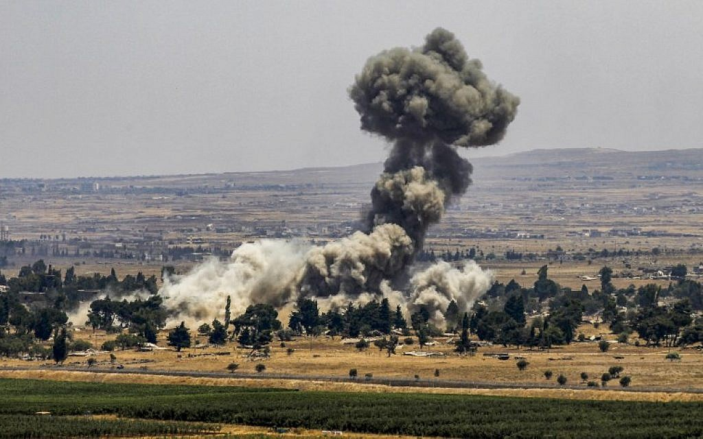 A picture taken on July 22, 2018 from the Israeli Golan Heights shows a smoke plume rising across the border in Quneitra in southwestern Syria, as rebels destroy their arms stocks prior to their departure. (AFP / JALAA MAREY)