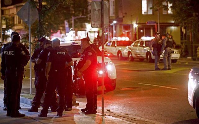 Toronto Police officers walk the scene at Danforth St. at the scene of a shooting in Toronto, Ontario, Canada on July 23, 2018. (AFP /Cole BURSTON)