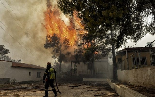 A firefighter tries to extinguish hotspots during a wildfire in Kineta, near Athens, Greece, on July 23, 2018. (VALERIE GACHE/AFP)